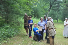 A shooter demonstrating how to load a muzzle loader to some visitors